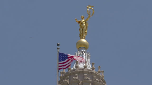 a flag waves in front of the dome and statue at the top of the harrisburg capital building in pa - 長点の映像素材/bロール