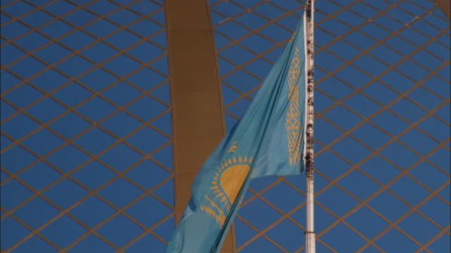 a flag waves in the wind at the ak orda presidential palace in astana kazakhstan. available in hd. - kazakhstan stock videos and b-roll footage