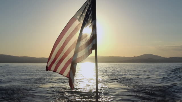 usa flag with sunset on the water - back lit stock videos & royalty-free footage