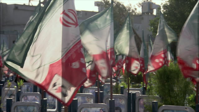 stockvideo's en b-roll-footage met ms td flags and graves with photographs at iraq war cemetery, esfahan, iran - graven