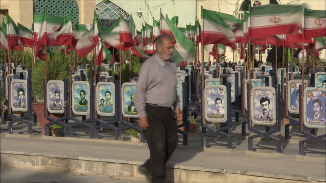 stockvideo's en b-roll-footage met ms flags and graves with photographs at iraq war cemetery, esfahan, iran - graven