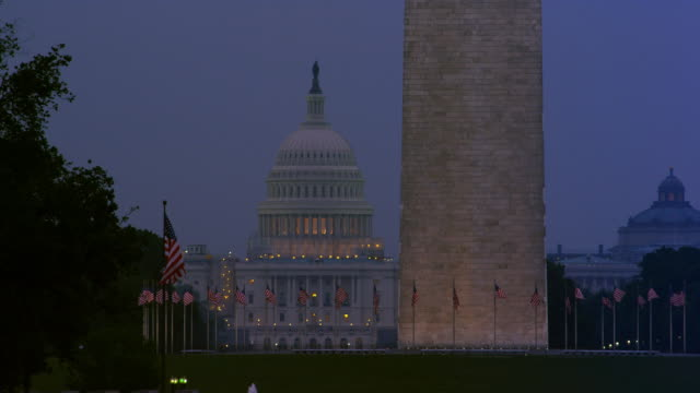 Flags around the base of the Washington Monument at dusk, US Capitol Building in background. Shot in 2012.