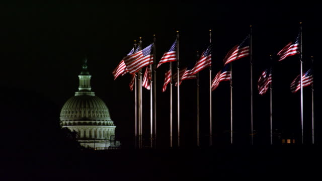 Flags at the base of the Washington Monument at night, US Capitol Dome in background. Shot in 2012.