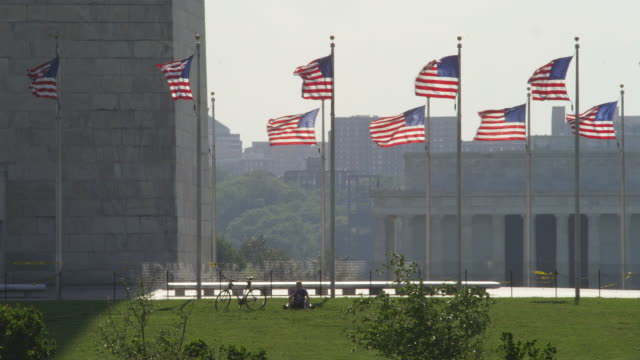 Flags at the base of the Washington Monument, man and bicycle on grass. Shot in May 2012.