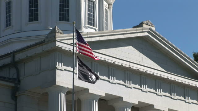 vidéos et rushes de flags flapping in front of capital building in montpelier vermont united states - capitole d'état du vermont