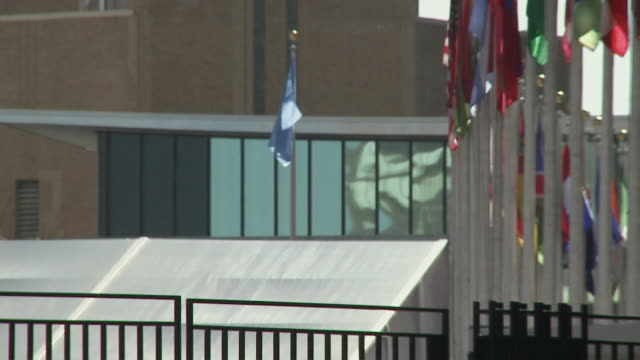 Flags flapping in wind in front of United Nations building / New York City New York USA
