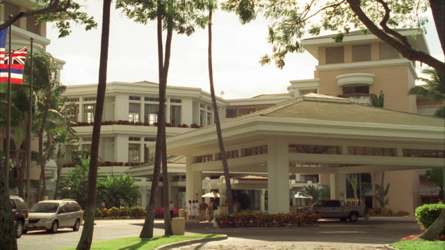 vidéos et rushes de flags flutter in the wind near the entrance of the grand wailea hotel and resort. - palace