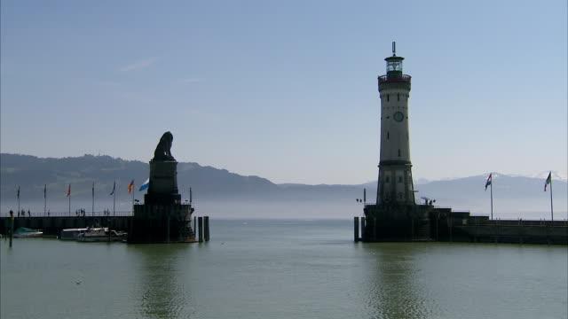 vidéos et rushes de flags flutter near a stone monument and lighthouse. - lighthouse