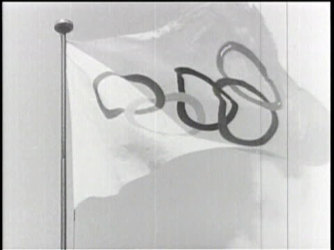 stockvideo's en b-roll-footage met flags fly above berlin as the city prepares for the 1936 olympic games/ olympic flag swaying in the wind/ pillared monument shown with nazi flags/... - 1936