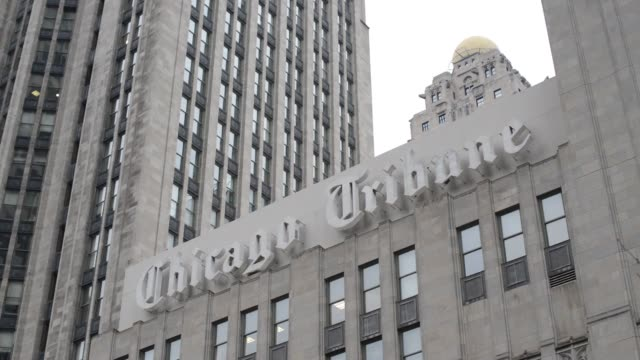 flags fly in front of chicago tribune signage displayed on the side of the tribune tower in chicago illinois us close up shots of the chicago tribune... - tribune tower stock-videos und b-roll-filmmaterial