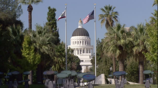 Flags fly in front of the California State Capitol.