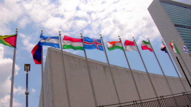 flags fly in front of the united nations headquarters in new york city. - 本部点の映像素材/bロール
