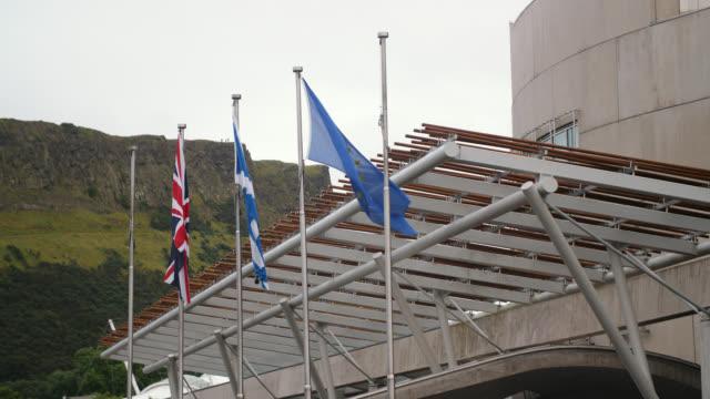 flags fly outside scottish parliament, edinburgh - scottish flag stock videos & royalty-free footage
