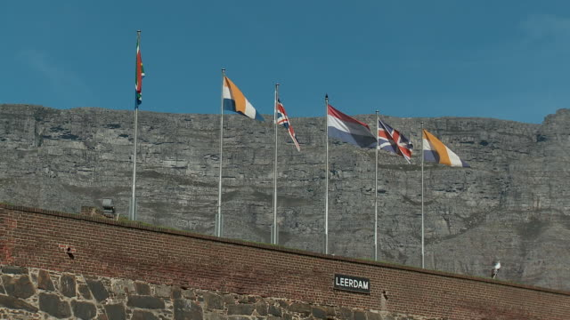 ws la flags flying over castle wall, cape town, western cape, south africa - rock face stock videos and b-roll footage