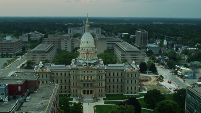 flags flying over michigan state capitol - lansing stock videos & royalty-free footage