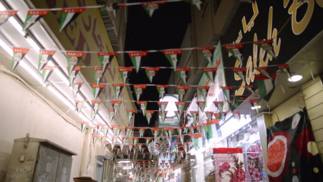 flags hang from banner over alley - deira, dubai - gasse stock-videos und b-roll-filmmaterial