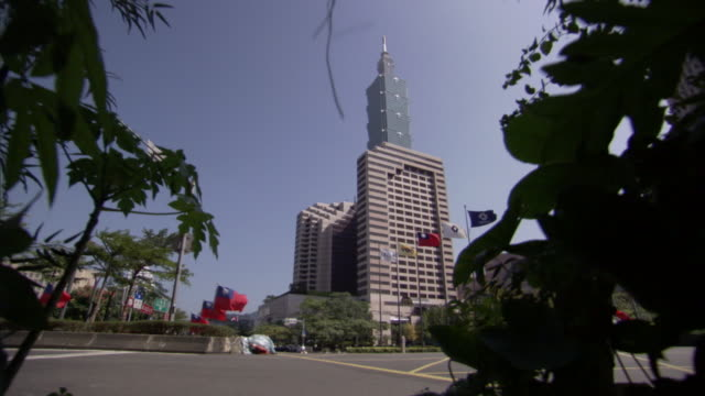 flags line a street and flap in the wind below taipei 101 skyscraper. - insel taiwan stock-videos und b-roll-filmmaterial