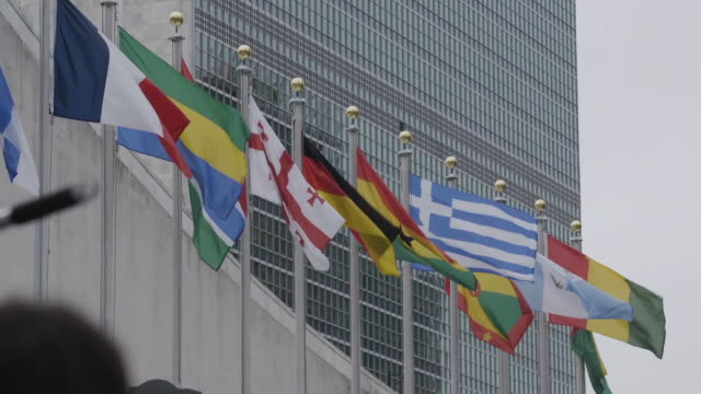 flags of united nations flying - vereinte nationen stock-videos und b-roll-filmmaterial