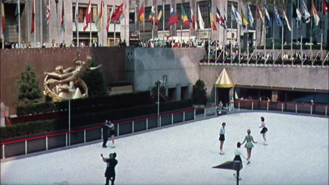 flags representing various countries surround the ice skating rink at rockefeller center. - rockefeller center video stock e b–roll
