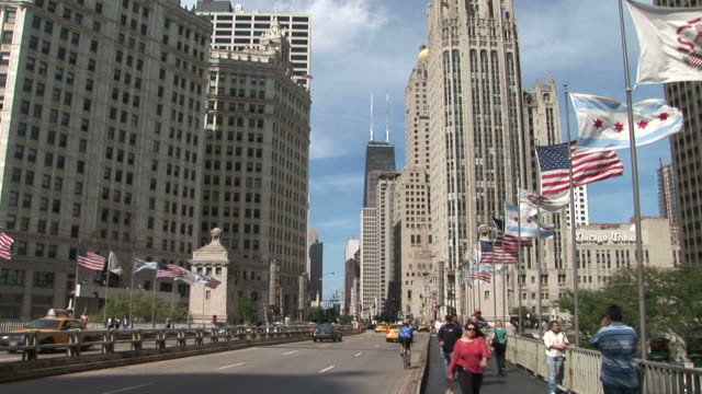 Flags wave along the Michigan Avenue Bridge near the Tribune Tower in Chicago United States