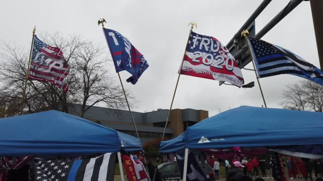 vidéos et rushes de flags wave in the cold wind outside a campaign rally for u.s. president donald trump at capital region international airport october 27, 2020 in... - lansing