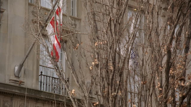 ZO Flags waving in the breeze on the Hay-Adams hotel, through bare tree branches / Washington, D.C., United States