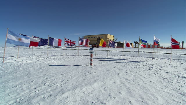 ws flags waving in wind around the ceremonial south pole with amundsen-scott south pole station in background / antarctica - antarctica research stock videos & royalty-free footage