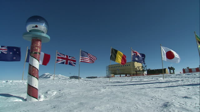 ms flags waving in wind around the ceremonial south pole with amundsen-scott south pole station in background / antarctica - south pole stock videos & royalty-free footage