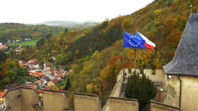 flags waving on karlštejn castle (hhrad karlštejn, burg karlstein) in bohemia - tschechische kultur stock-videos und b-roll-filmmaterial