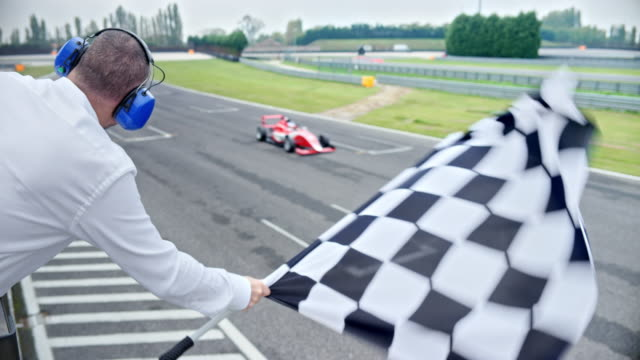 vídeos de stock e filmes b-roll de ld flagsman waving the chequered flag as the formula drivers cross the finish line - competição