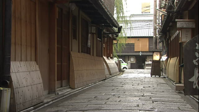 a flagstone alley passes between buildings in the gion district of kyoto. - gion stock videos and b-roll footage
