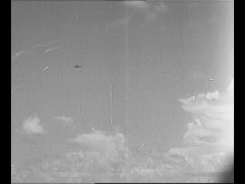 WS flak in air from World War II Battle of Midway military ships in background ship on right fires with flashes emitting / tracer bullets aim at...