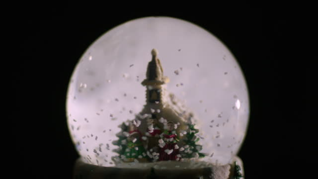 flakes of 'snow' swirl around a plastic church and people in victorian-style outfits contained within a snow globe before coming to a stop. - palla dell'albero di natale video stock e b–roll