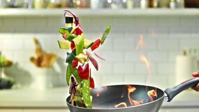 slo mo tu flambaying colorful vegetables - vegetable stock videos & royalty-free footage