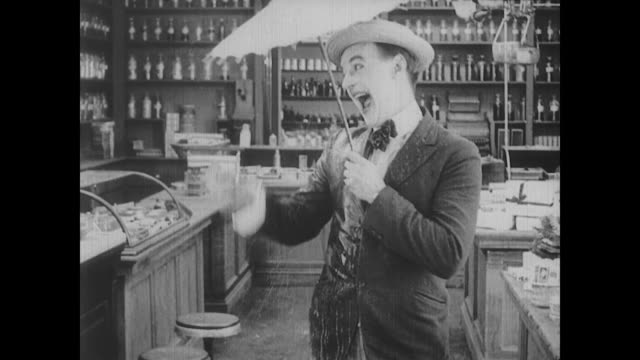 1917 a flamboyant customer bathes in perfume to the dismay of a drugstore clerk (fatty arbuckle) - parfum stock-videos und b-roll-filmmaterial