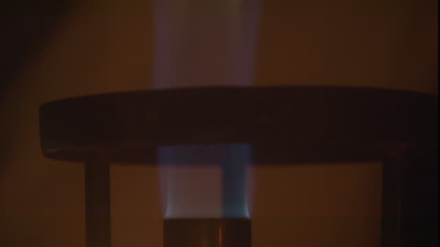 a flame flickers on a bunsen burner. - bunsen burner stock videos & royalty-free footage