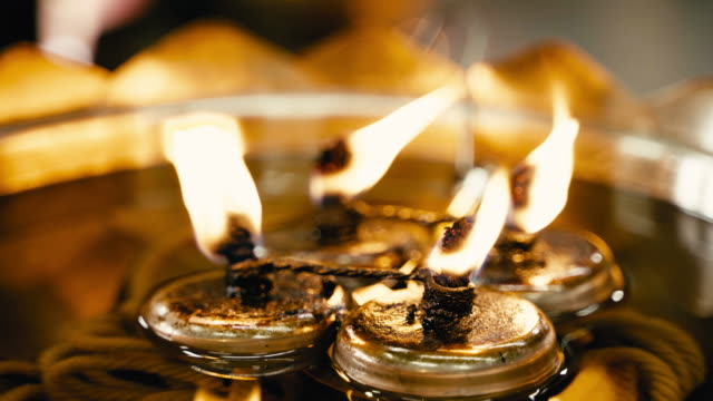 flame from burning oil candle lamp in shrine. - incense stock videos & royalty-free footage