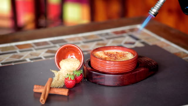 Flame from torch burning sugar on creme brulee