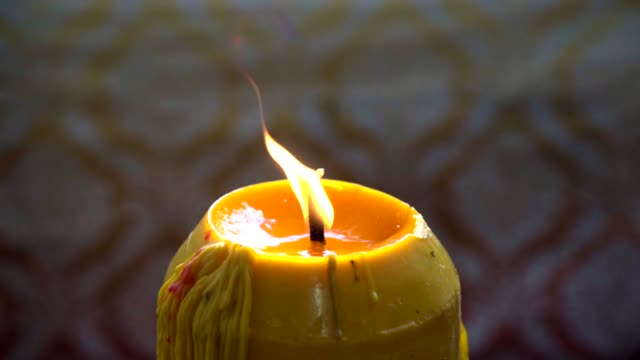 vídeos de stock e filmes b-roll de flame on candle in thai temple in slow motion. - incenso