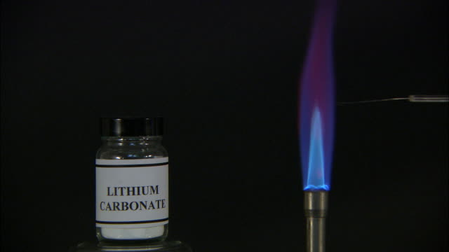 a flame test used in chemistry to detect the presence of certain metal ions, based on each elements characteristic emission spectrum (lithium carbonate) - western script stock videos & royalty-free footage