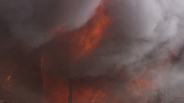 Flames and heavy smoke fill the interior of a burning structure