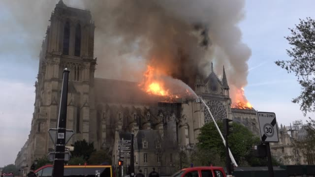 flames and smoke are seen billowing from the roof at notre-dame cathedral april 15, 2019 in paris, france. a fire broke out on monday afternoon and... - notre dame de paris stock videos & royalty-free footage