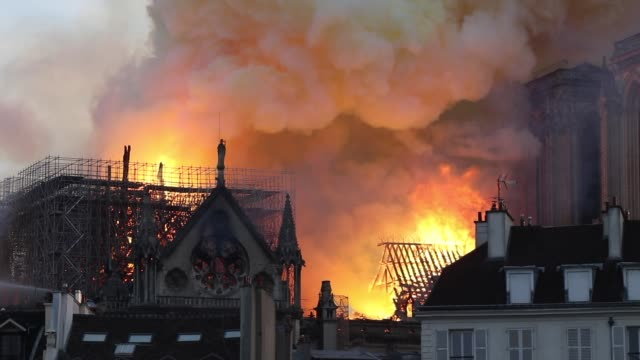 flames and smoke are seen billowing from the roof at notre-dame cathedral on april 15, 2019 in paris, france. a fire broke out on monday afternoon... - notre dame de paris stock videos & royalty-free footage