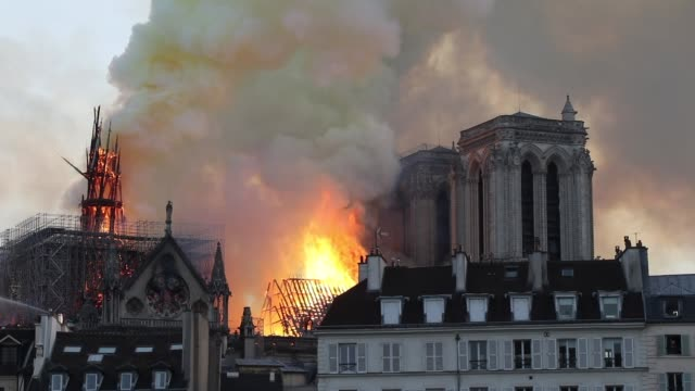 flames and smoke are seen billowing from the roof at notredame cathedral on april 15 2019 in paris france a fire broke out on monday afternoon and... - turmspitze stock-videos und b-roll-filmmaterial