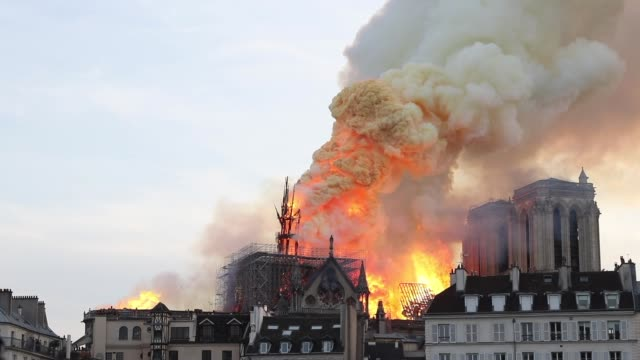 flames and smoke are seen billowing from the roof at notredame cathedral on april 15 2019 in paris france a fire broke out on monday afternoon and... - spira tornspira bildbanksvideor och videomaterial från bakom kulisserna