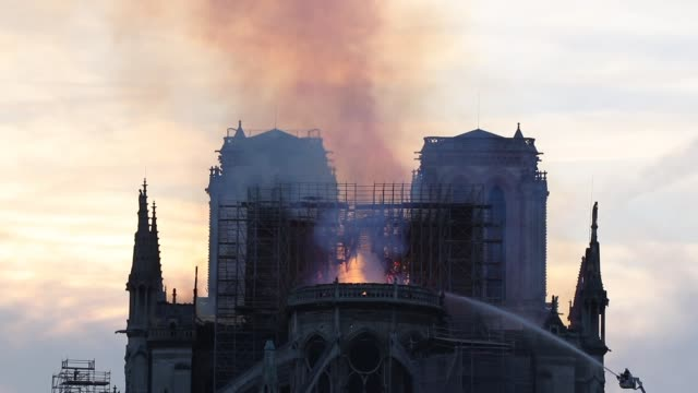 flames and smoke are seen billowing from the roof at notre-dame cathedral on april 15, 2019 in paris, france. a fire broke out on monday afternoon... - 國際名勝 個影片檔及 b 捲影像