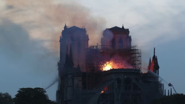flames and smoke are seen billowing from the roof at notredame cathedral on april 15 2019 in paris france a fire broke out on monday afternoon and... - notre dame de paris stock videos & royalty-free footage