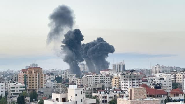 flames and smoke billow following early morning airstrikes on gaza city - striscia di gaza video stock e b–roll