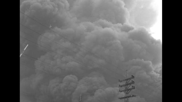 stockvideo's en b-roll-footage met flames and thick smoke rising from standard oil refinery / four firemen with their truck parked on road near refinery / two shots of flames and smoke... - fire hose
