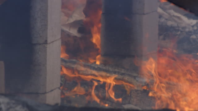 flames and thin smoke drift around concrete foundation pillars after a structure fire - myrtle creek stock videos & royalty-free footage